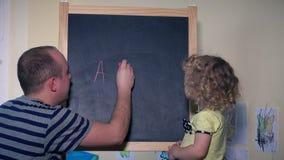 Πατέρας με τις επιστολές εκμάθησης παιδιών κοριτσιών κορών μικρών παιδιών του abc στον πίνακα κιμωλίας απόθεμα βίντεο