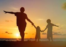 Πατέρας με τις σκιαγραφίες παιδιών που έχουν τη διασκέδαση στο ηλιοβασίλεμα Στοκ φωτογραφίες με δικαίωμα ελεύθερης χρήσης