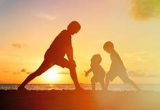 Πατέρας με τις σκιαγραφίες παιδιών που έχουν τη διασκέδαση στο ηλιοβασίλεμα Στοκ Εικόνα