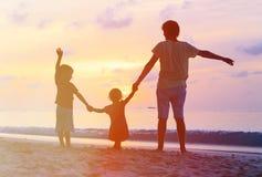 Πατέρας με τις σκιαγραφίες παιδιών που έχουν τη διασκέδαση στο ηλιοβασίλεμα Στοκ Φωτογραφία