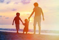 Πατέρας με τις σκιαγραφίες παιδιών που έχουν τη διασκέδαση στο ηλιοβασίλεμα Στοκ Εικόνες