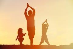 Πατέρας με τις σκιαγραφίες παιδιών που έχουν τη διασκέδαση στο ηλιοβασίλεμα Στοκ Φωτογραφίες
