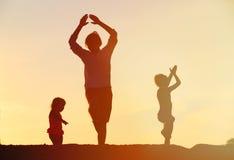 Πατέρας με τις σκιαγραφίες παιδιών που έχουν τη διασκέδαση στο ηλιοβασίλεμα Στοκ εικόνα με δικαίωμα ελεύθερης χρήσης