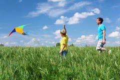 Πατέρας με το γιο το καλοκαίρι με τον ικτίνο στοκ φωτογραφία
