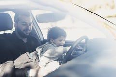 Πατέρας με το γιο playng στο αυτοκίνητο που οδηγεί πίσω από το γυαλί Στοκ Φωτογραφίες