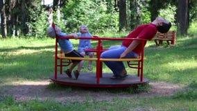 Πατέρας με το γύρο δύο παιδιών στο ιπποδρόμιο στο θερινό πράσινο πάρκο απόθεμα βίντεο