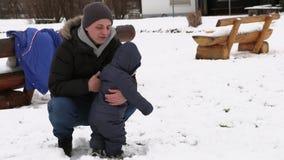 Πατέρας με το μικρό γιο του που παίζει στο χιόνι φιλμ μικρού μήκους