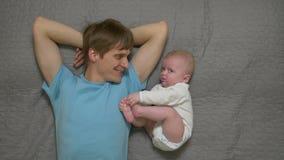 Πατέρας με το μωρό στο κρεβάτι απόθεμα βίντεο