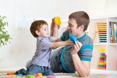 Πατέρας με το παιχνίδι αγοριών παιδιών στοκ εικόνες