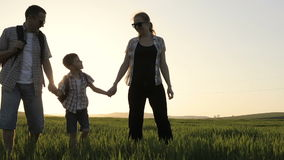 Πατέρας, μητέρα και γιος που περπατούν στον τομέα στο χρόνο ηλιοβασιλέματος φιλμ μικρού μήκους
