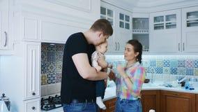 Πατέρας, μητέρα και νεογέννητο αγοράκι στο άσπρο εσωτερικό κουζινών απόθεμα βίντεο