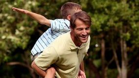 Πατέρας που δίνει ένα σηκώνω στην πλάτη στο γιο του απόθεμα βίντεο