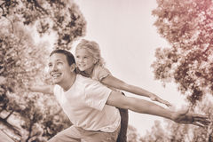 Πατέρας που δίνει στην κόρη ένα σηκώνω στην πλάτη στο πάρκο στοκ εικόνα με δικαίωμα ελεύθερης χρήσης