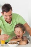 Πατέρας που δίνει τα δημητριακά στο γιο του Στοκ φωτογραφία με δικαίωμα ελεύθερης χρήσης