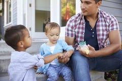Πατέρας που δίνει την καραμέλα παιδιών στα βήματα έξω από τη μάνικα Στοκ φωτογραφίες με δικαίωμα ελεύθερης χρήσης