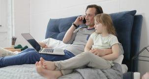 Πατέρας που αγκαλιάζει την κόρη μιλώντας στη συνεδρίαση τηλεφωνήματος μαζί στο lap-top χρήσης κρεβατιών στην κρεβατοκάμαρα απόθεμα βίντεο