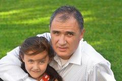 Πατέρας που αγκαλιάζει την οικογενειακή φωτογραφία κορών στον κήπο Στοκ φωτογραφίες με δικαίωμα ελεύθερης χρήσης