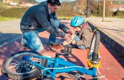 Πατέρας που βάζει τη ζώνη ασβεστοκονιάματος πέρα από το τραυματισμό γονάτου Στοκ φωτογραφίες με δικαίωμα ελεύθερης χρήσης