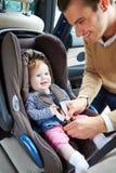 Πατέρας που βάζει το μωρό στο κάθισμα αυτοκινήτων στοκ φωτογραφίες