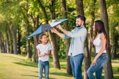 Πατέρας που βοηθά την κόρη για να προωθήσει έναν ικτίνο ξοδεύοντας το χρόνο από κοινού στοκ εικόνες με δικαίωμα ελεύθερης χρήσης