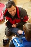 Πατέρας που βοηθά το γιο για να βάλει στις θερμές υπαίθριες μπότες στοκ εικόνα με δικαίωμα ελεύθερης χρήσης