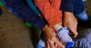 Πατέρας που βοηθά το γιο του για να βάλει τις κάλτσες επάνω στην κρεβατοκάμαρα στο σπίτι 4k φιλμ μικρού μήκους