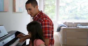 Πατέρας που διδάσκει την κόρη του για να παίξει το πιάνο 4k φιλμ μικρού μήκους