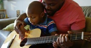 Πατέρας που διδάσκει το γιο του πώς να παίξει την κιθάρα στο σπίτι 4k απόθεμα βίντεο