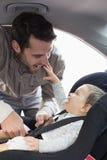 Πατέρας που εξασφαλίζει το μωρό στο κάθισμα αυτοκινήτων Στοκ φωτογραφία με δικαίωμα ελεύθερης χρήσης