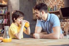 Πατέρας που εξετάζει χαριτωμένος λίγο γιο που πίνει το φρέσκο χυμό από πορτοκάλι Στοκ Εικόνες