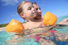 Πατέρας που διδάσκει την κόρη της πώς να κολυμπήσει με armbands Στοκ Εικόνα
