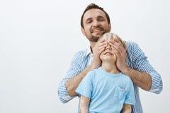 Πατέρας που κάνει την έκπληξη στο γιο σε birhday Πορτρέτο του φροντίζοντας αγαπώντας μπαμπά που καλύπτει τα μάτια παιδιών με τους στοκ φωτογραφία με δικαίωμα ελεύθερης χρήσης