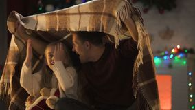 Πατέρας που λέει τη συναρπαστική ιστορία Χριστουγέννων για τη συνεδρίαση μικρών κοριτσιών κάτω από το άνετο καρό φιλμ μικρού μήκους