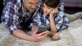 Πατέρας που παρουσιάζει στο γιο αστεία εφαρμογή στο smartphone, χρόνος εξόδων από κοινού στοκ εικόνα με δικαίωμα ελεύθερης χρήσης