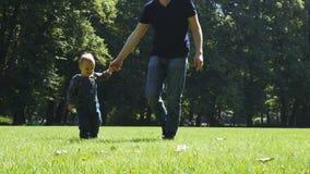 Πατέρας που περπατά στο θερινό πάρκο με το γιο του απόθεμα βίντεο