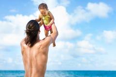 Πατέρας που πετά το παιδί του παιχνιδιάρικα στην παραλία στοκ εικόνα