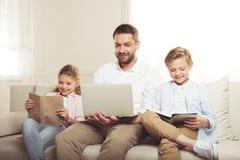 Πατέρας που χρησιμοποιεί το lap-top ενώ βιβλία και η συνεδρίαση ανάγνωσης κορών του και γιων στον καναπέ Στοκ φωτογραφία με δικαίωμα ελεύθερης χρήσης