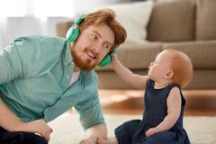 Πατέρας στα ακουστικά με την κόρη μωρών στο σπίτι Στοκ φωτογραφία με δικαίωμα ελεύθερης χρήσης