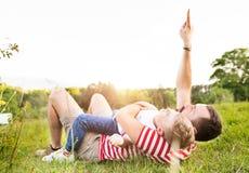 Πατέρας Hipster και λίγος γιος στο πράσινο λιβάδι καλοκαίρι ημέρας ηλιόλουστο Στοκ Φωτογραφία
