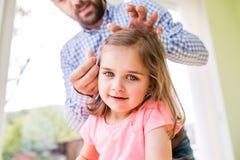Πατέρας Hipster με την κόρη του, που ορίζει την τρίχα της, στο εσωτερικό Στοκ φωτογραφία με δικαίωμα ελεύθερης χρήσης