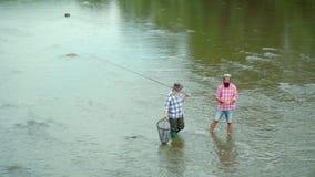 Πατέρων και γιων Ψαράς μυγών που χρησιμοποιεί τη ράβδο αλιείας μυγών στον όμορφο ποταμό Οικογένεια και παραγωγή - καλοκαιρινές δι απόθεμα βίντεο