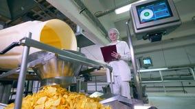 Πατατάκια πατατών που περιέρχονται σε ένα εμπορευματοκιβώτιο ενώ ένας βιομηχανικός εργάτης ελέγχει μια διαδικασία απόθεμα βίντεο
