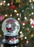 Πατινάζ Santa πάγου σε μια σφαίρα χιονιού με το δέντρο στο υπόβαθρο Στοκ Εικόνες