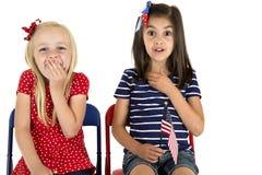 Πατριωτικά κορίτσια που κρατούν μια αμερικανική σημαία με τις αστείες εκφράσεις Στοκ Εικόνες