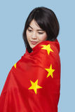 Πατριωτική νέα γυναίκα που τυλίγεται στην κινεζική σημαία πέρα από το μπλε υπόβαθρο Στοκ Φωτογραφία