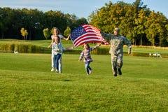 Πατριωτική οικογένεια που τρέχει με την τεράστια αμερικανική σημαία Στοκ Φωτογραφίες