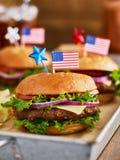 Πατριωτικός τα burgers με τις αμερικανικές σημαίες στοκ φωτογραφία με δικαίωμα ελεύθερης χρήσης