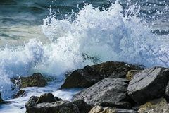 Παφλασμοί από τα κύματα ενάντια στη δύσκολη ακτή Στοκ Φωτογραφία