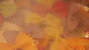 Παφλασμός ζυμαρικών μακαρονιών που περιέρχεται στο βρασμένο νερό, την ιταλικές διατροφή και την έννοια υγειονομικής περίθαλψης απόθεμα βίντεο