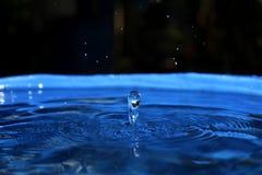 Παφλασμός νερού στο μπλε υπόβαθρο στοκ φωτογραφία με δικαίωμα ελεύθερης χρήσης